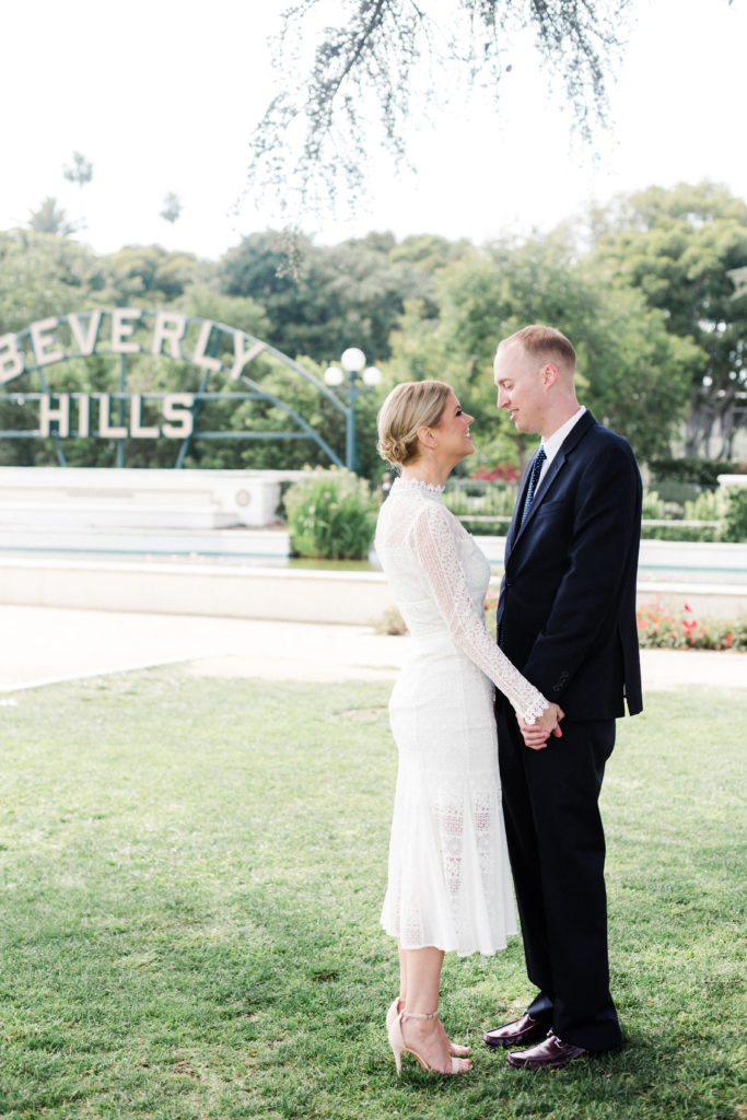 bride and groom in front of beverly hills sign