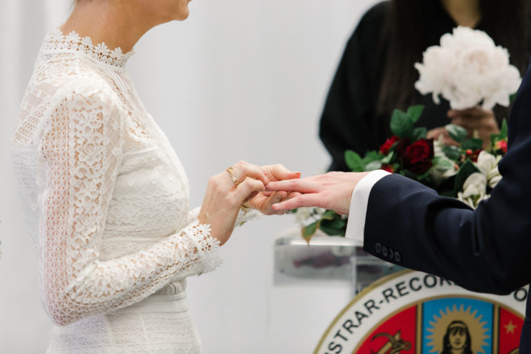bride puts ring on groom