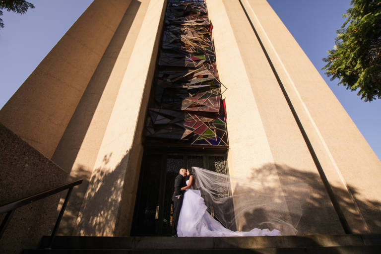 bride and groom kiss outside church