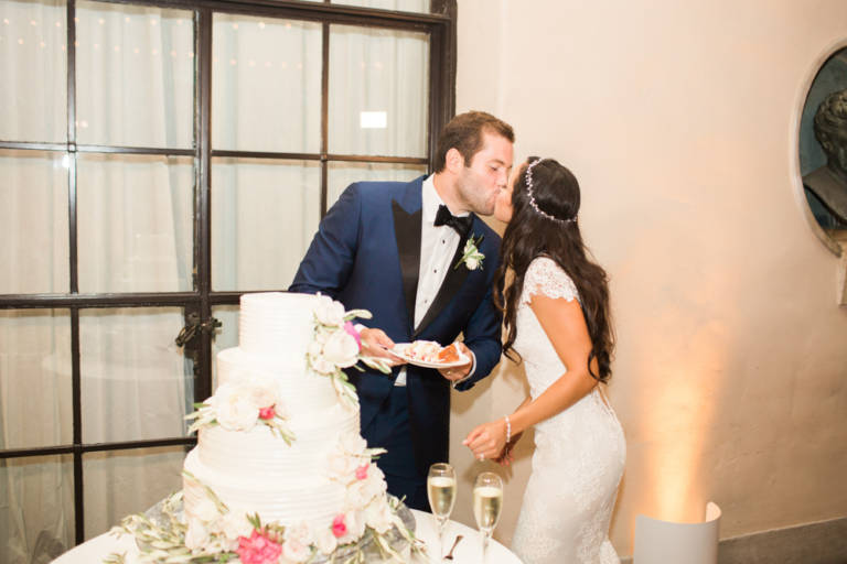 bride and groom kiss while cutting cake