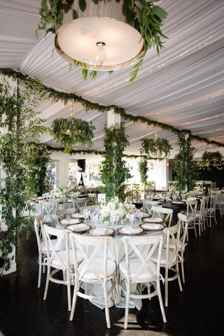 wedding reception in tent with greenery