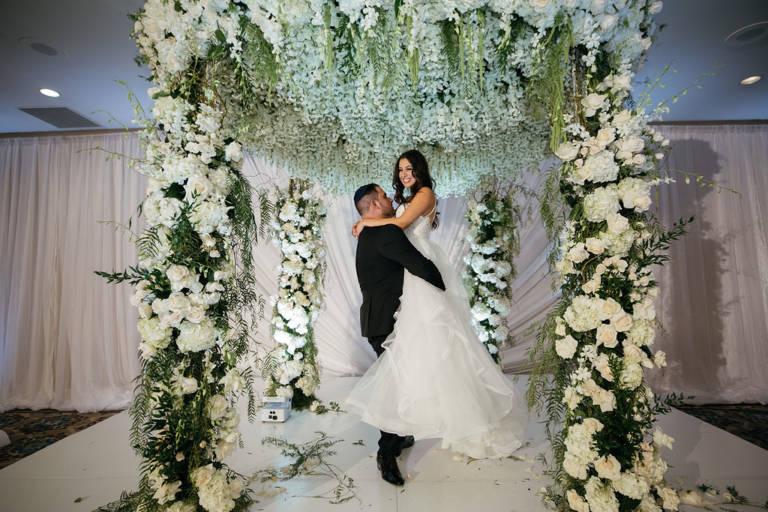 groom lifts bride under chuppah