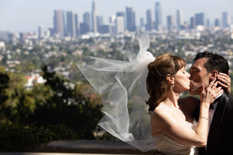 bride and groom kiss with view of downtown los angeles