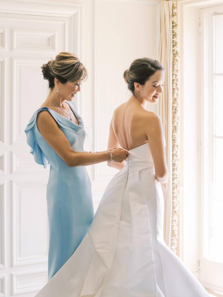 mother fastens brides dress