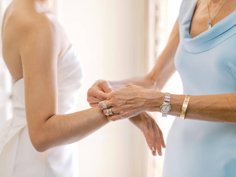 mother puts on bride's bracelet