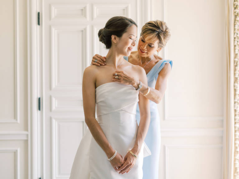 mother of the bride helps bride get ready
