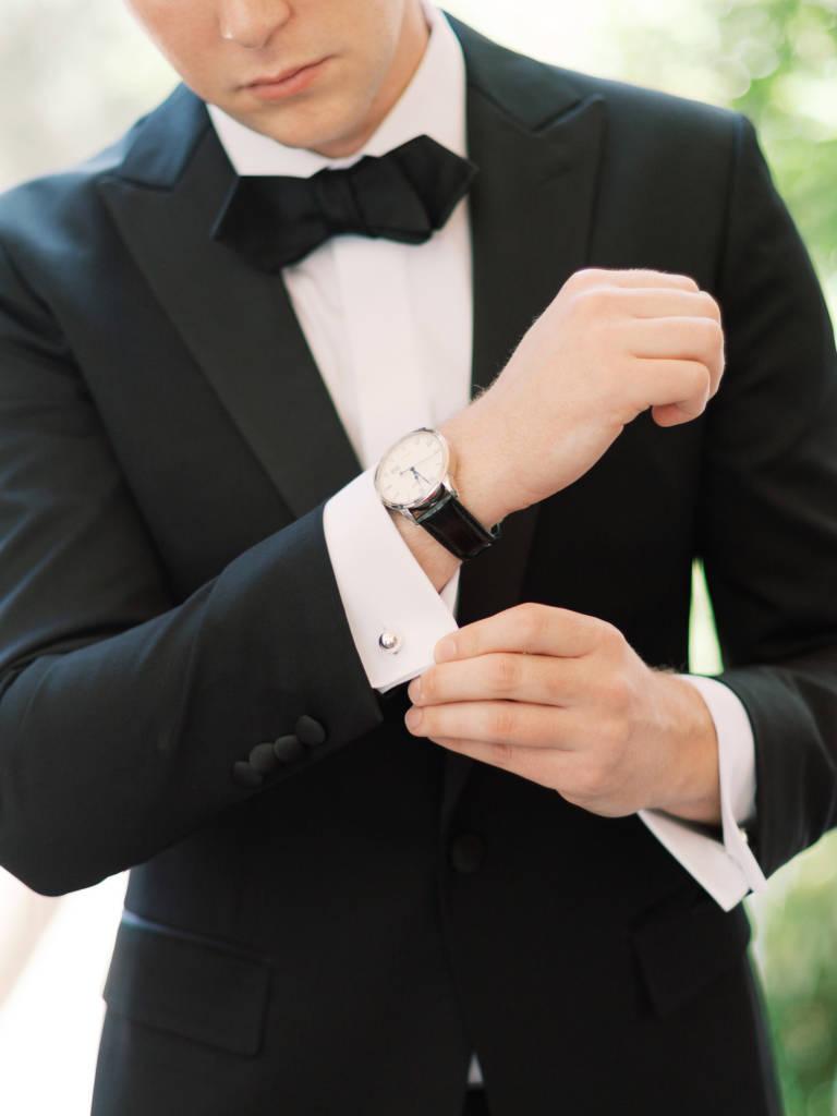 groom fastens cufflinks