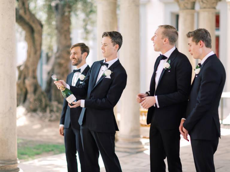 groomsmen pop champagne