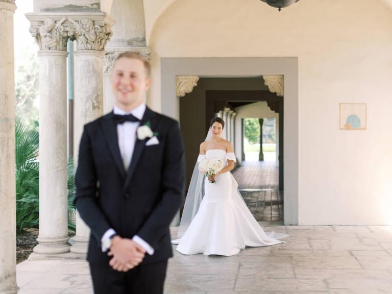 bride walks up behind groom