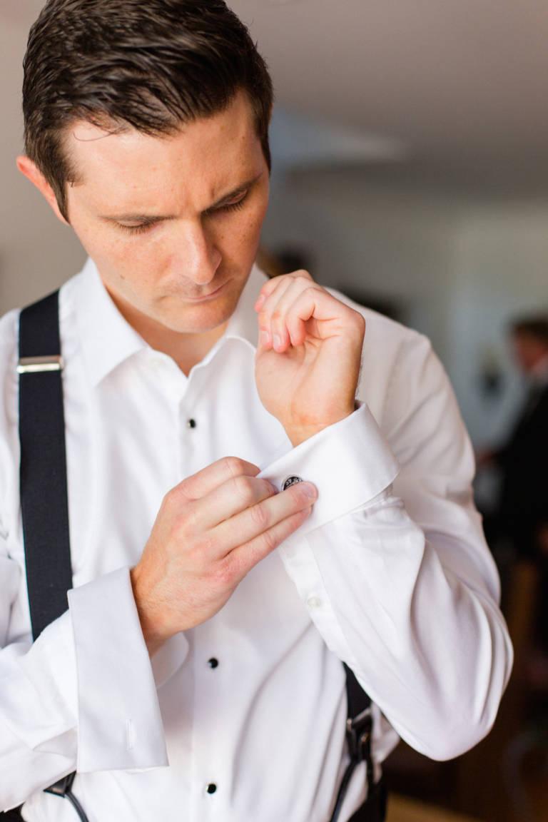 groom puts on cufflinks