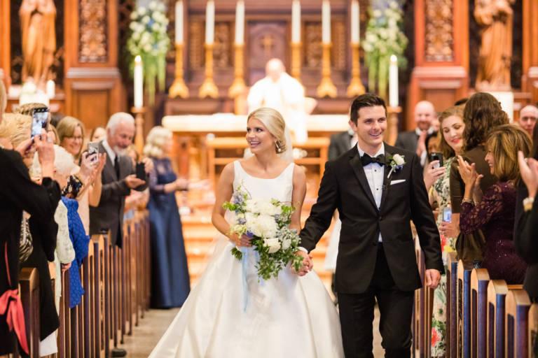 bride and groom walk down church aisle