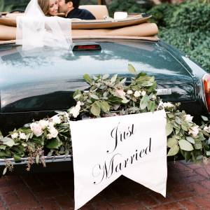 bride and groom in vintage car with just married sign